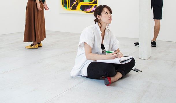 Woman sits on the floor in front of a work of art in a museum and makes notes in her sketch book.