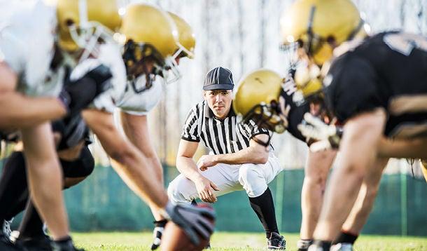 Referee looks at footballers on footballfield