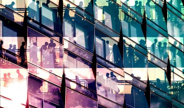 Gekleurd licht valt op de glazen gevel van een kantoorgebouw