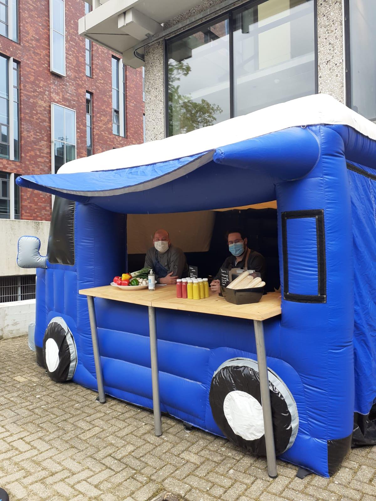 Blauwe opblaasbare foodtruck op het campusplein, met erin twee medewerkers van de cateraar Eurest die mondkapjes dragen.