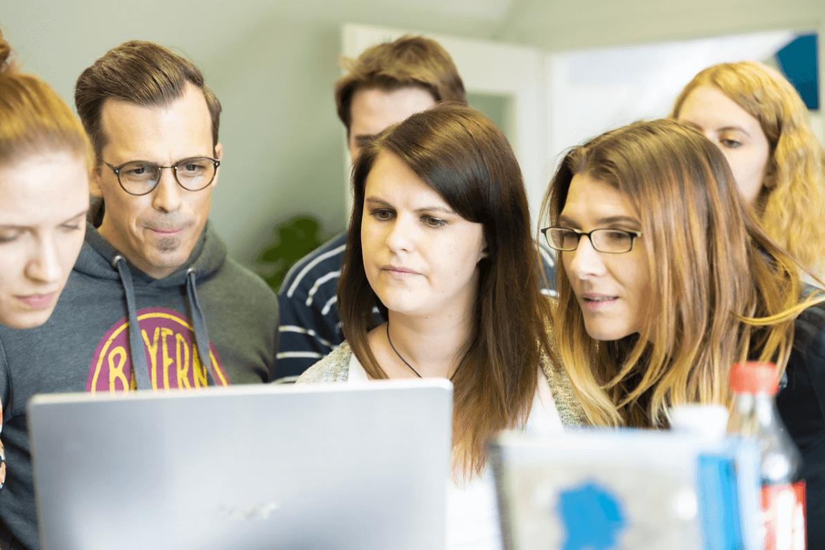 Beeld: ScienceGuide - zes docenten buigen zich over één laptop