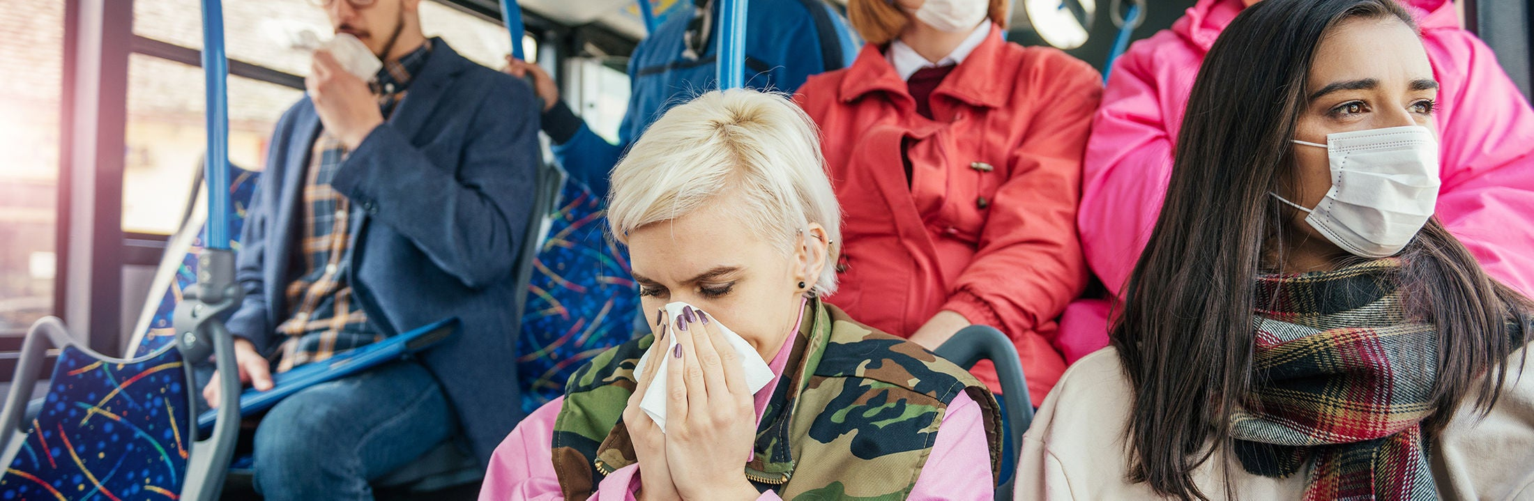 People wearing masks in public transport, one of them is blowing her nose