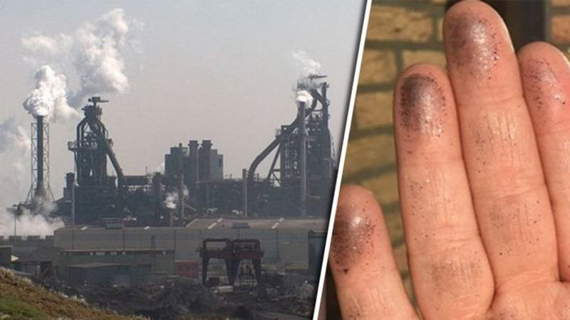 Hand with black dust on the fingers and industrial area with smoking chimneys.