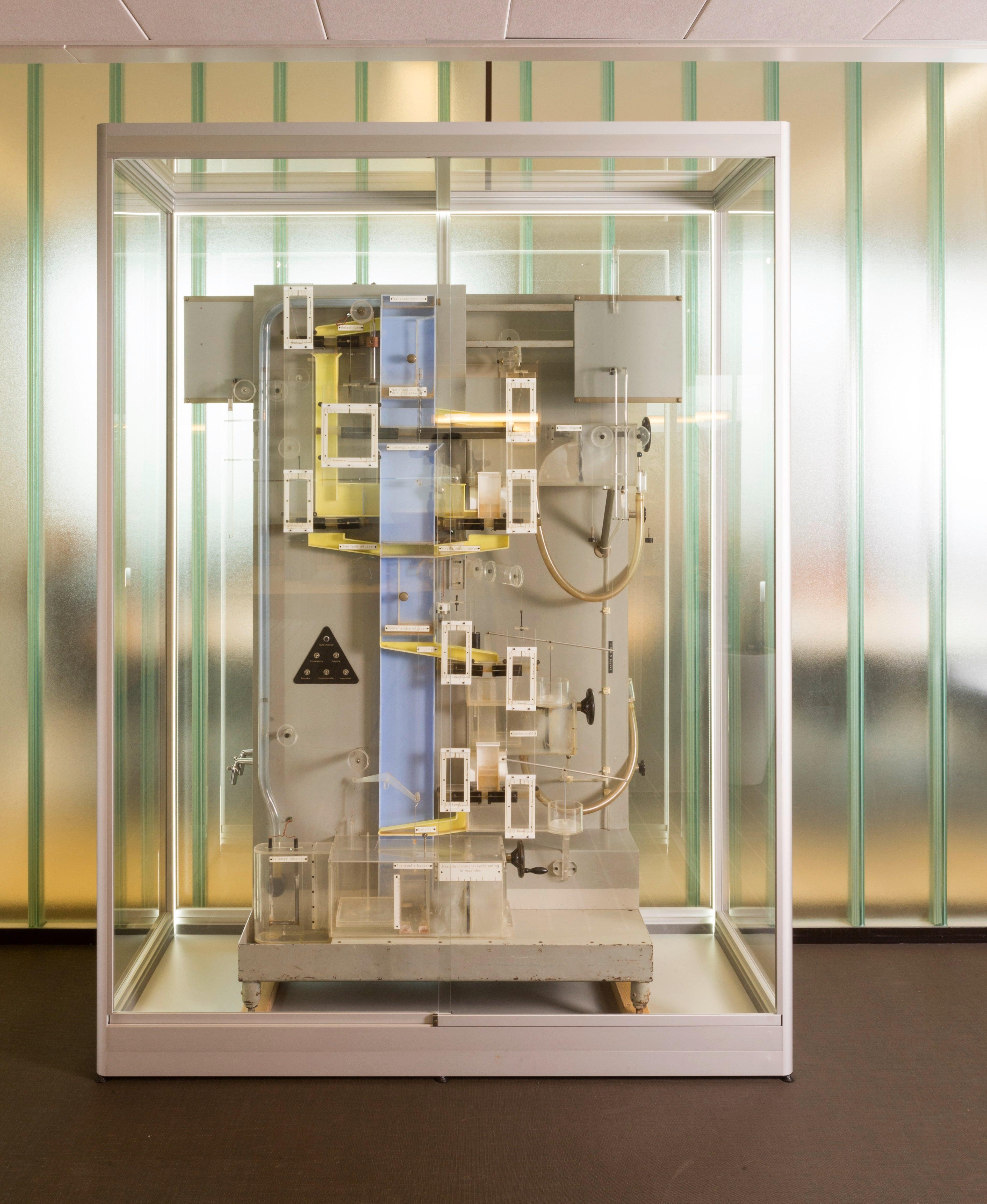 Machine in een vitrine tegen een witte achtergrond. De machine bestaat uit schuifjes, leidingen waardoor een circulair traject afgelegd kan worden met water om de circulaire economie te verbeelden.