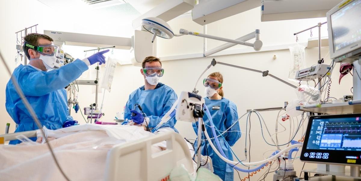Artsen met maskers helpen COVID patient
