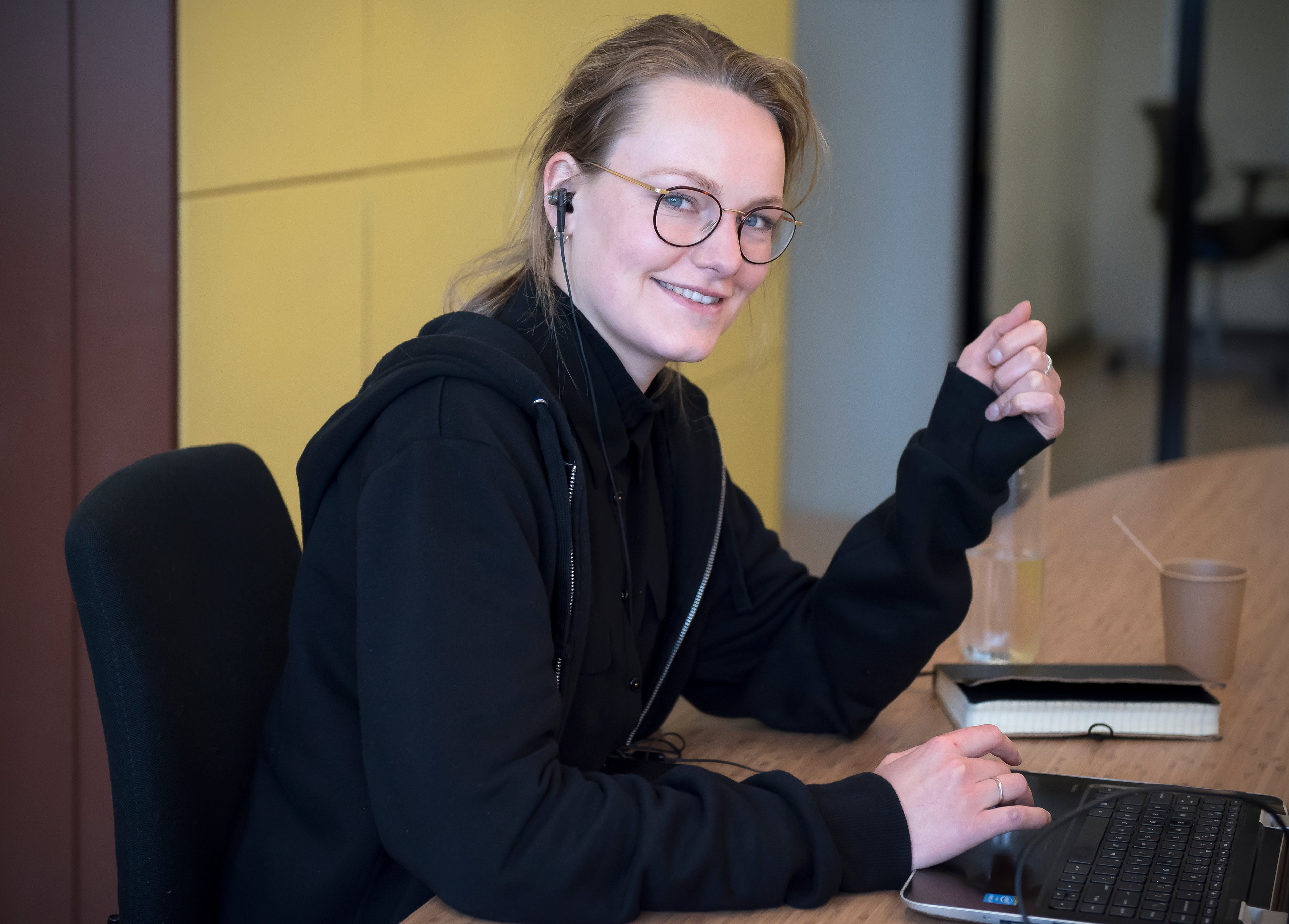 Blond meisje met bril in zwart shirt zit aan bureau en kijkt camera in van opzij
