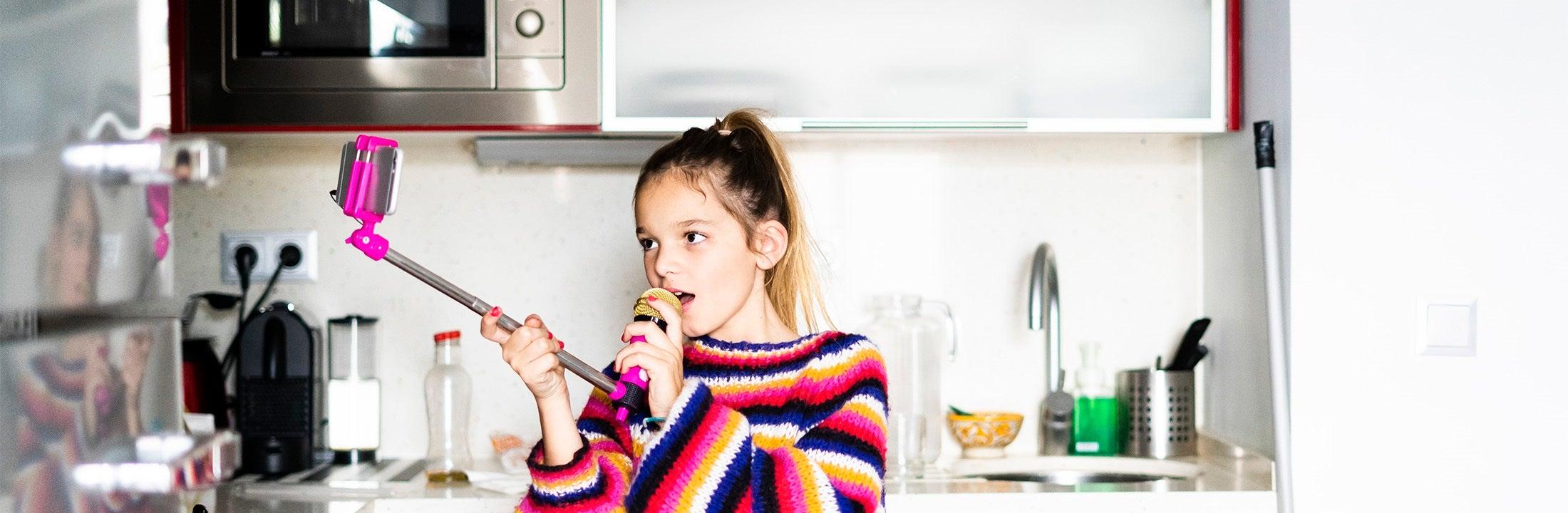 Meisje in de keuken met microfoon en telefoon op selfiestick zet zichzelf op de foto
