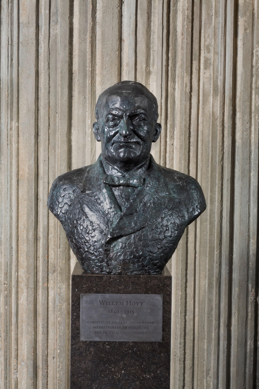 Bronzen borstbeeld van een man op een zwarte sokkel tegen een houten latten achtergrond