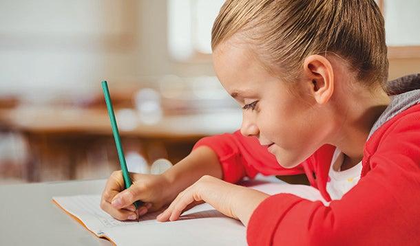 Kind schrijft in een schrift