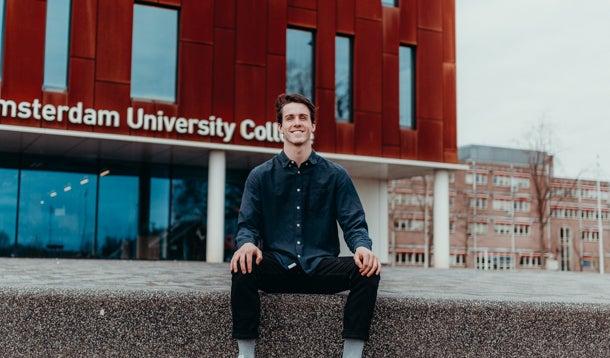 Student voor de ingang van het gebouw van Amsterdam University College