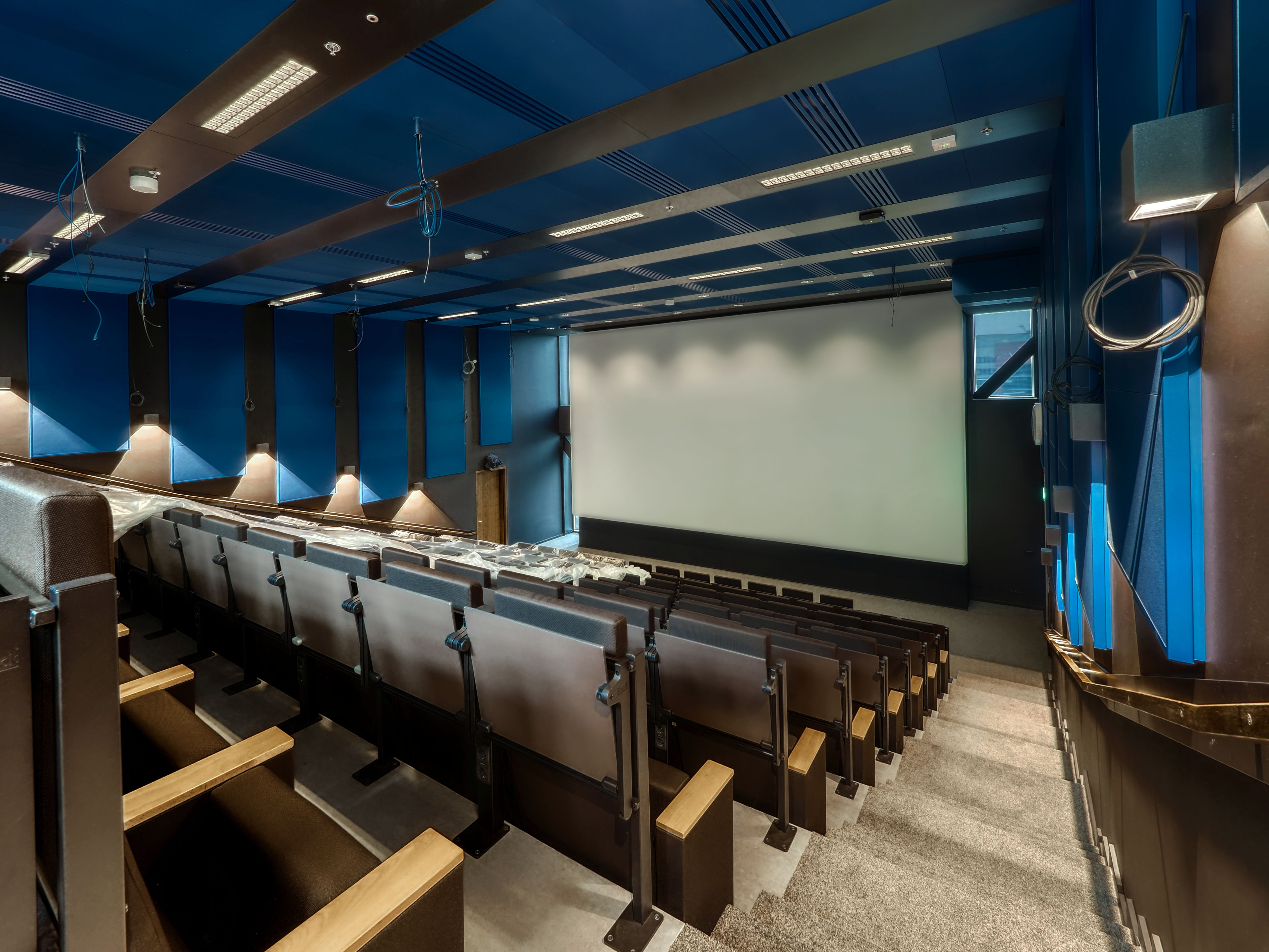 Photograph of the new theatre of Rialto in the NU Building. The seats are empty and the screen is white. The decoration looks industrial, with blue walls and a blue ceiling.