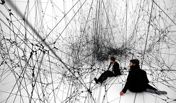Two men sit in a gigantic black spider web (sculpture by Tomas Saraceno)