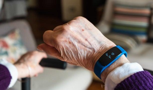 Een oudere vrouw draagt een polshorloge met hartslagmeter