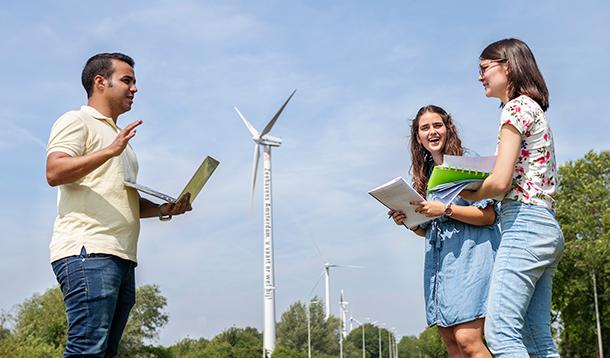 Drie studenten zijn buiten in overleg met op de achtergrond een windmolen