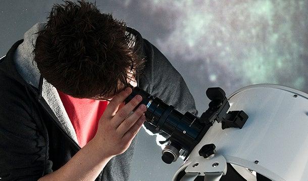 Student kijkt door telescoop