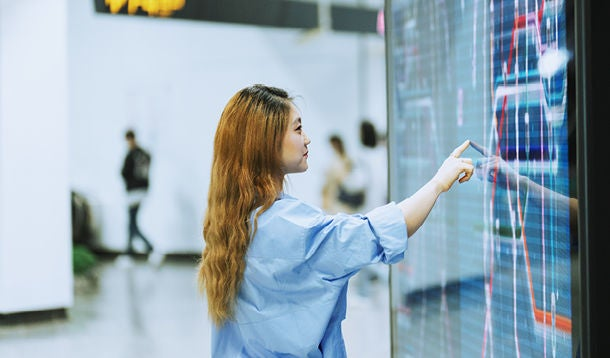 A student touches a large touch screen