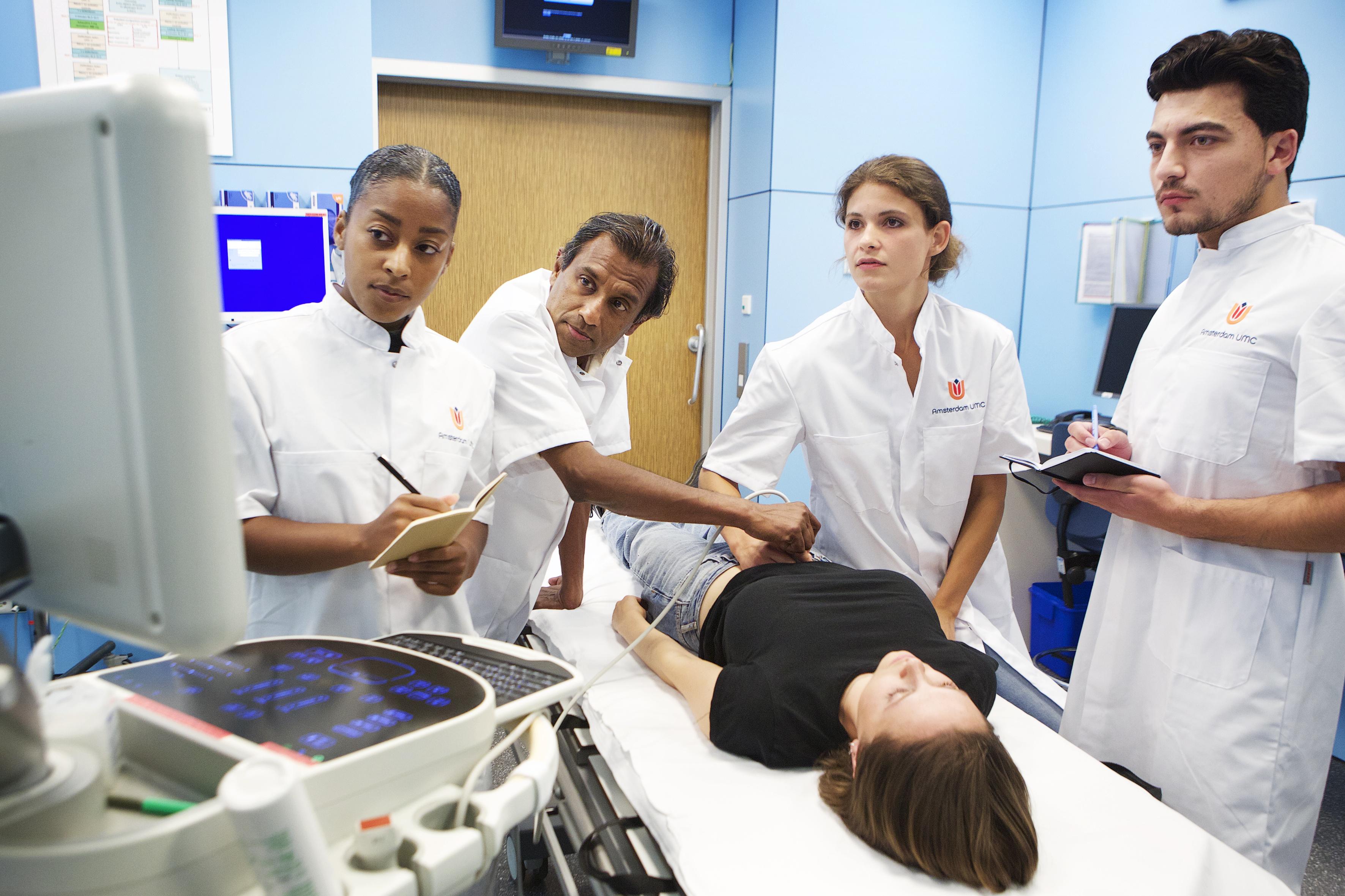 Dokter en 3 coassistenten voeren een echo uit op een patient