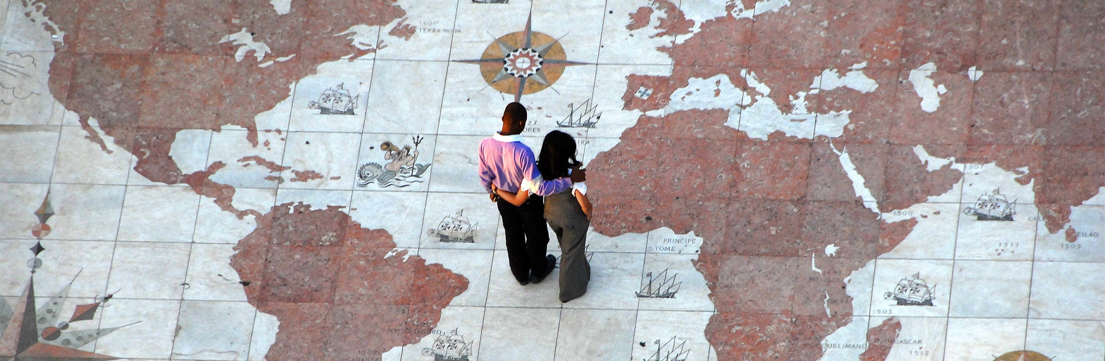 A man and a woman are standing on a monument in Lissabon that marks the main routes of the Portuguese expansion