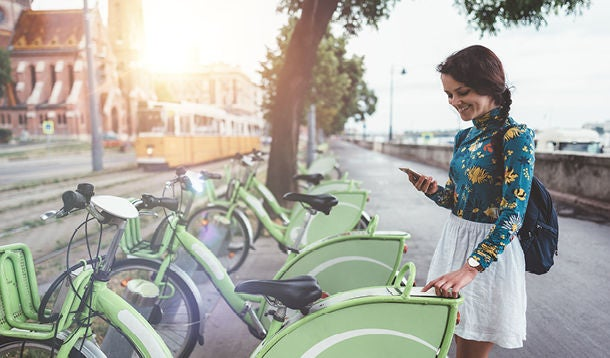 A young woman enters a code on a display on a rental bicycle
