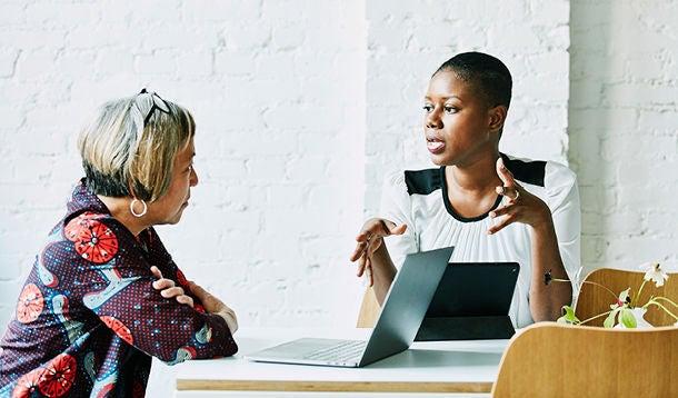 Twee vrouwen in gesprek in een kantoorsetting