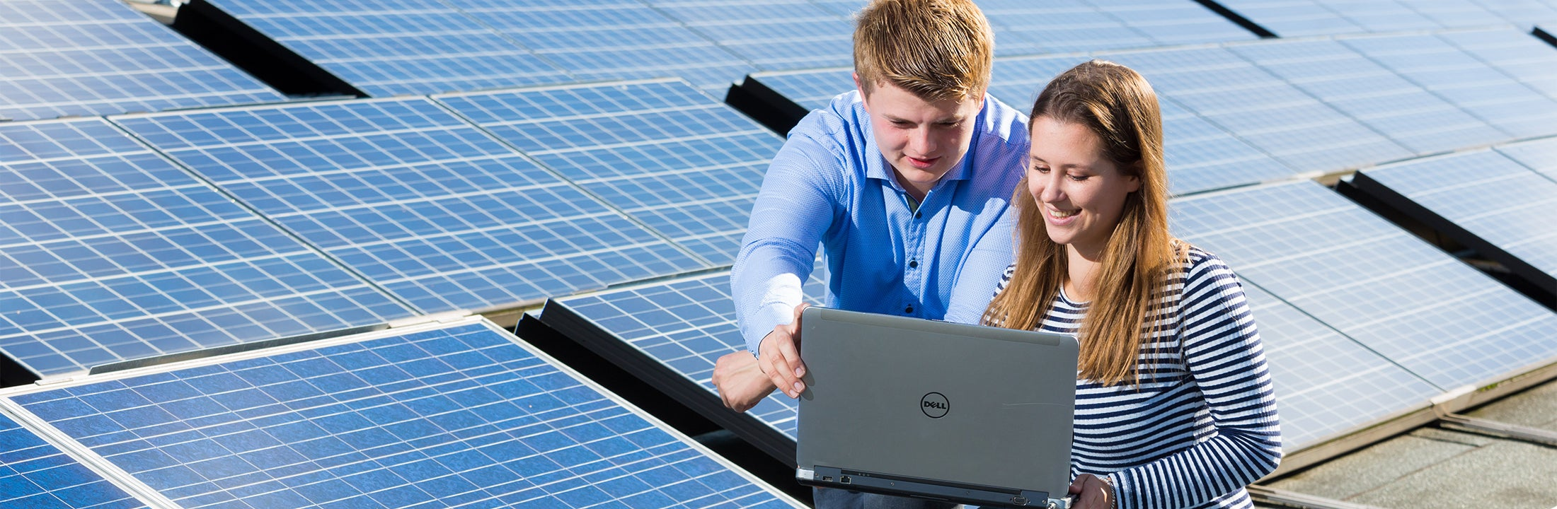 Two students surrounded by solar panels