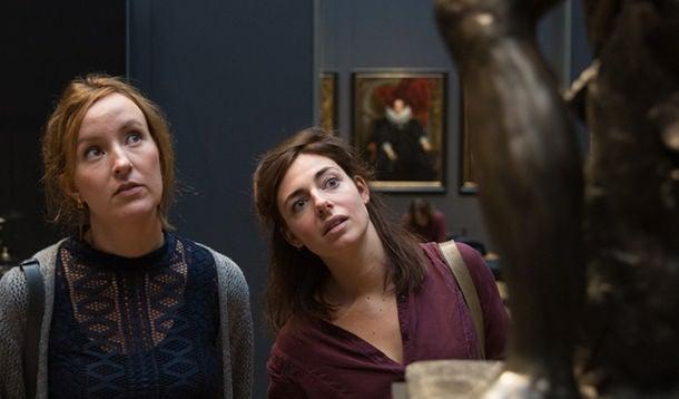 2 jonge vrouwen kijken geïnteresseerd naar een kunstwerk