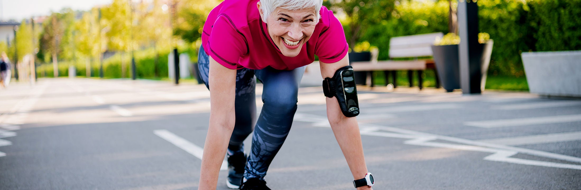 A sporty elderly woman in running clothes is ready to sprint on the open road